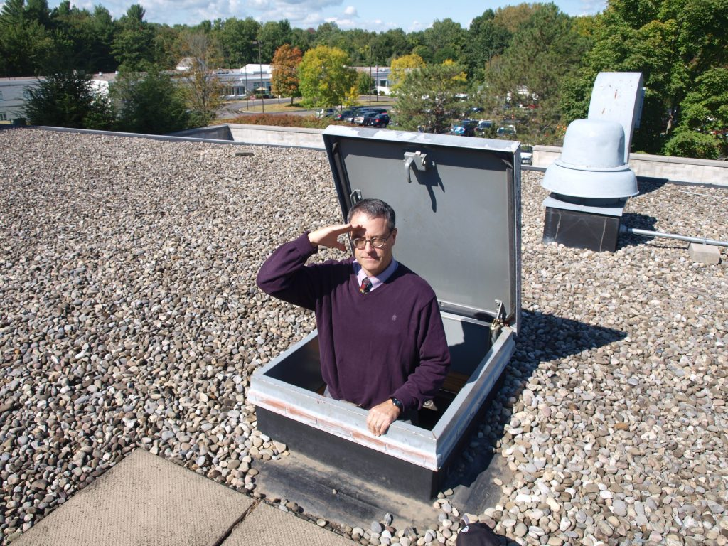 Library director peers out of roof hatch.